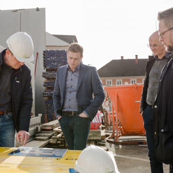 Bernhard Pointinger zeigt Stefan Kaineder die Plaene auf der Baustelle DMP 8